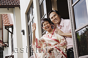 Asia Images Group - Mature couple smiling and waving at camera