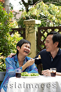 Asia Images Group - Mature couple laughing while dining in restaurant