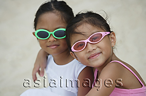 Asia Images Group - Two young sisters with sunglasses hugging