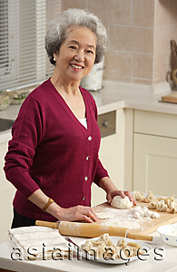 Asia Images Group - Elderly woman baking in the kitchen