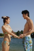 Young couple on beach holding hands, looking at each other - Marcus Mok