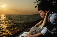 Young couple sitting on rocks overlooking beach - Marcus Mok