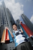 A man looks at the camera as he holds up shopping bags - Marcus Mok