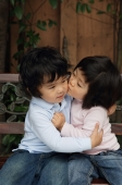 Young girl kissing young boy cheek - Tony Metaxas