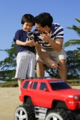 Father and son at the beach with remote controlled toy - Yukmin