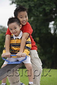 AsiaPix - Two brothers sitting on See-Saw, smiling at camera