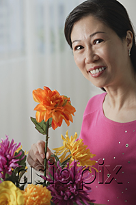 AsiaPix - Mature woman holding flowers, smiling at camera, portrait