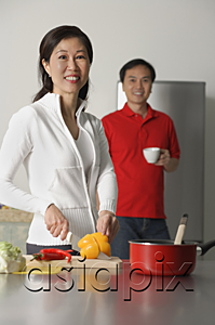 AsiaPix - Mature woman in kitchen preparing a meal, man standing behind her, both looking at camera