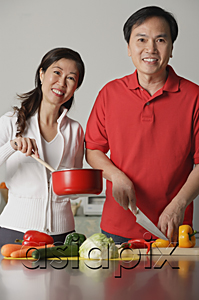 AsiaPix - Mature couple in kitchen, preparing a meal together, smiling at camera