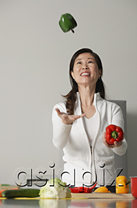 AsiaPix - Woman in kitchen, juggling vegetables