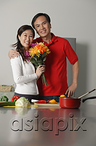 AsiaPix - Mature couple in kitchen, embracing, woman holding bouquet of flowers