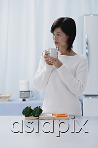 AsiaPix - Woman in kitchen, holding mug, looking away