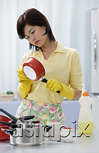 AsiaPix - Woman in kitchen, cleaning pots and pans