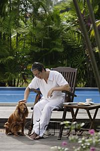 AsiaPix - Mature man sitting by swimming pool, petting his dog