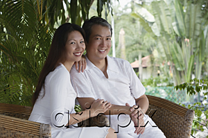 AsiaPix - Couple sitting on rattan chairs, looking at camera, smiling