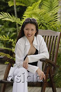 AsiaPix - Woman sitting in garden, smiling at camera, portrait