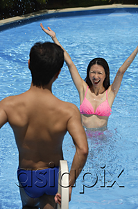 AsiaPix - Woman in swimming pool, arms outstretched, looking at man standing in front of her