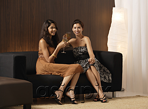 AsiaPix - Two girls sitting on couch holding champagne, toasting, smiling at camera