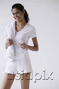AsiaPix - Woman standing, smiling, looking at camera, holding water bottle and towel over shoulder