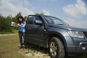 AsiaPix - Woman standing next to SUV, looking at map