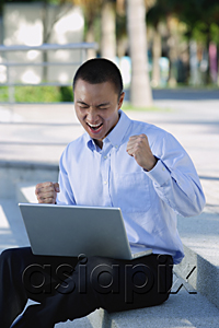 AsiaPix - A man is excited as he uses his laptop outdoors