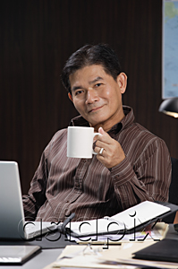 AsiaPix - A man having a drink while working at his desk