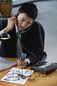 AsiaPix - A man sits at his desk with lots of phones