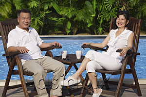 AsiaPix - Couple relaxing in deck chairs by the pool