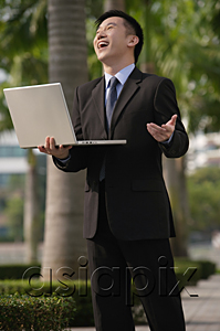 AsiaPix - Businessman holding laptop and laughing