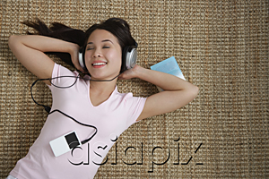 AsiaPix - Young woman listening to music while lying down