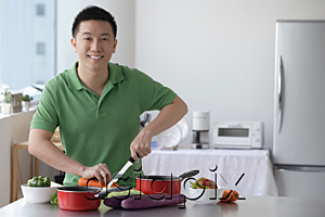 AsiaPix - Man cutting vegetable and smiling at camera