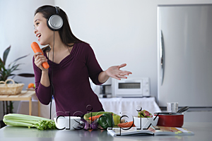 AsiaPix - Young woman singing into carrot