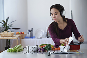 AsiaPix - Young woman cooking while listening to music
