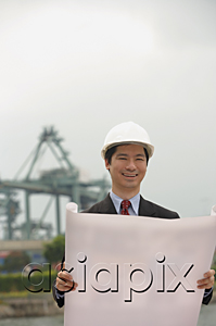 AsiaPix - Engineer with plans and hard helmet looking at camera