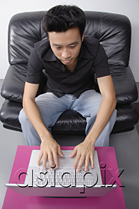 AsiaPix - Young man sitting on couch using laptop