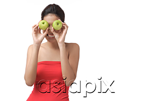 AsiaPix - Young woman holding two apples over eyes
