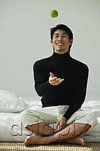 AsiaPix - Young man sitting on bed, throwing apple in the air