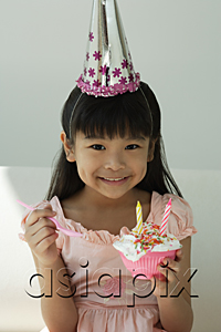 AsiaPix - Birthday girl with cupcake and spoon on hand smiling at camera