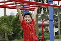 Boy using the jungle gym at playground - Asia Images Group