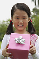 Girl holding pink wrapped gift box, smiling - Asia Images Group