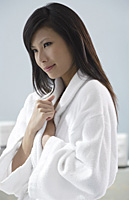 woman wearing bathrobe, thinking, relaxed - Asia Images Group