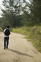 Man walking down dirt road, hiking, back to camera - Asia Images Group