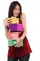 Young woman holding four presents, smiling at camera - Asia Images Group