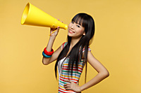 Young woman holding yellow megaphone and smiling at camera - Asia Images Group