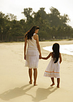 Mother and daughter walking hand and hand on beach, wearing white dresses - Asia Images Group