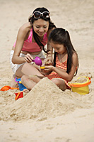 Mother and daughter building sand castle on beach - Asia Images Group