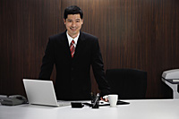 A businessman stands behind his desk - Asia Images Group