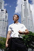 A man with a helmet stands in front of skyscrapers - Asia Images Group