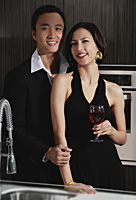 A couple smile at the camera while in the kitchen - Asia Images Group
