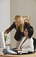 Two woman look at a computer while at work - Asia Images Group